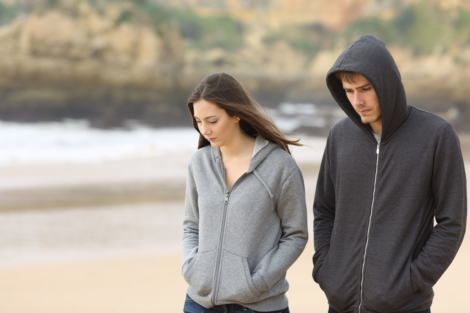Couple of angry and sad teenagers together walking on the beach